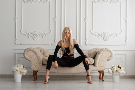 Foto de Sexy beautiful young model woman in fashionable black clothes with jeans sitting on a sofa in a vintage room - Imagen libre de derechos
