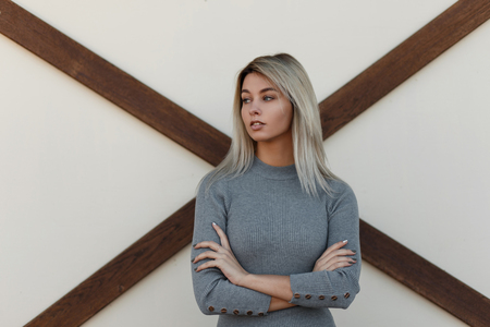 Photo pour Beautiful young stylish woman in vintage knitted gray sweater posing near a white wall with wooden timber. Fashionable girl stands in hand for hand pose - image libre de droit