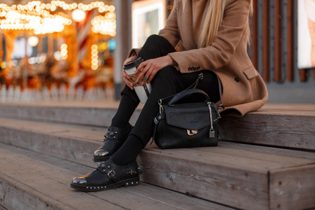 Photo pour Young girl in a vintage coat with a warm knitted sweater, stylish jeans, black leather fashionable modern shoes and a stylish leather bag sits with a cup of coffee. Women's stylish clothing. Close-up - image libre de droit