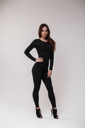 Photo pour Sexy attractive beautiful brown-haired woman in a black stylish T-shirt in stylish black leggings and leather sandals on his heels is standing and posing in a bright room on a white background. Girl - image libre de droit