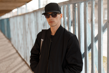 Foto de Young attractive serious hipster guy in black sunglasses in a stylish black jacket in a black cap near the background of a wooden fence. Stylish american guy. - Imagen libre de derechos