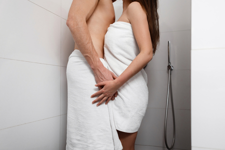 Handsome man with pretty woman standing in the shower and hugging. Young couple love and kiss.