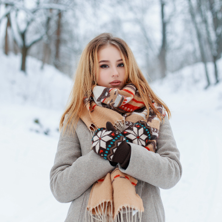 Foto de Modern charming young girl in a vintage warm coat in beautiful woolen mittens with a fashionable scarf with a red pattern posing outdoors on the background of snowy trees in the park. Stylish girl. - Imagen libre de derechos