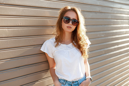 Photo for Young modern hipster woman in stylish sunglasses in a summer fashion white t-shirt in trendy jeans is standing near a wooden vintage wall on a sunny spring day. Cute girl resting outdoors. - Royalty Free Image