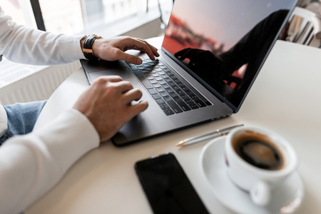 Photo pour Young professional businessman uses a laptop for work. Blogger works on the computer. Side view of the man's hands and the desktop, on which stands a modern laptop, a cup of coffee and a telephone. - image libre de droit