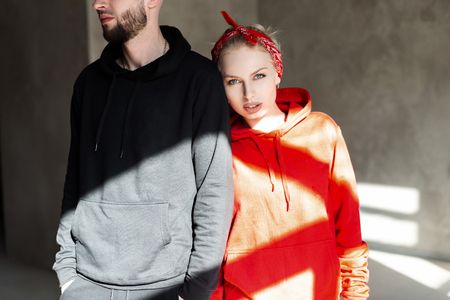 Photo pour Stylish beautiful fashionable couple in fashion black and red hoodie indoors with sunlight. Pretty hipster woman in a red hoodie standing near a style man in a black sweatshirt - image libre de droit