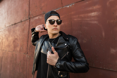 Photo pour Handsome young man hipster in a stylish leather black jacket in a trendy black cap in dark fashionable sunglasses in a black T-shirt stands near a vintage metal wall outdoors. Attractive guy model. - image libre de droit