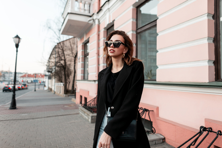 Foto de Fashionable modern young woman hipster in a black elegant coat in a T-shirt in jeans in stylish sunglasses walking down the street near vintage buildings. European girl travels around the city. Spring - Imagen libre de derechos