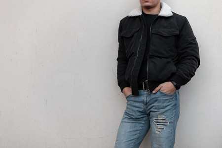 Foto de Young stylish man in a black trendy jacket with a white collar in vintage blue jeans in a black t-shirt stands near the gray wall. Fashionable men's outerwear. Street style. Close-up of a male body. - Imagen libre de derechos