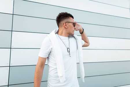 Photo pour Urban handsome young hipster man in a trendy white t-shirt in stylish sunglasses with fashionable hairstyle posing near a modern building in the city. Attractive guy  model outdoors. Summer style. - image libre de droit