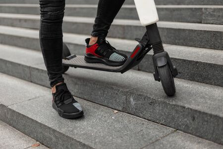 Photo for Men's legs in black jeans in sneakers are standing on an electric scooter. Fashionable guy is resting after riding a scooter standing on a vintage stone staircase in the city on a summer day.Close-up. - Royalty Free Image