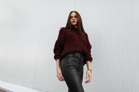 Photo pour Attractive young woman in a fashionable knitted sweater in stylish leather black pants poses near a modern white wall in the city. - image libre de droit