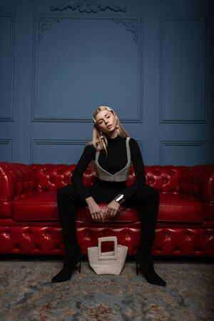 Foto de Glamorous young woman blonde in fashionable black clothes with a white pearl bag in high heel shoes in a white vintage pearl top sitting on a red leather sofa in the blue room. Sexy trendy girl model. - Imagen libre de derechos