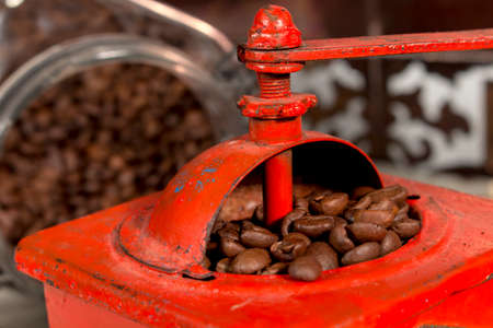 Roasted coffee beans being grinded in traditional style with an old manual coffee grinder
