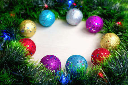 Photo pour Selective and soft focus of multi-colored shiny Christmas tree balls on wreath of green tinsel and burning electric lights on garland. New year's background and postcard. Holiday home decoration - image libre de droit