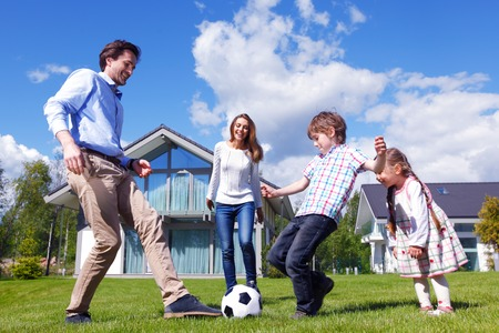 Foto de family playing football in front of their house - Imagen libre de derechos