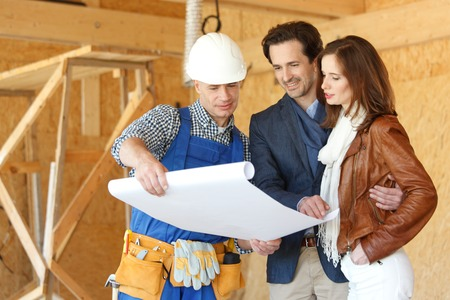Photo pour Worker shows house design plans to a young couple at construction site - image libre de droit