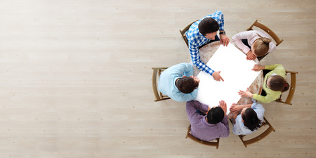 Foto de Hipster business teamwork brainstorming planning meeting concept, people team sitting around the table with white paper and pointing, copy space - Imagen libre de derechos