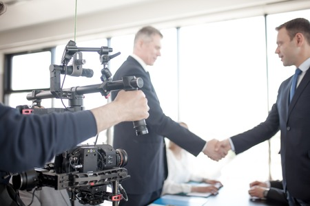 Photo for Videographer using steadycam, making video of business people shaking hands - Royalty Free Image