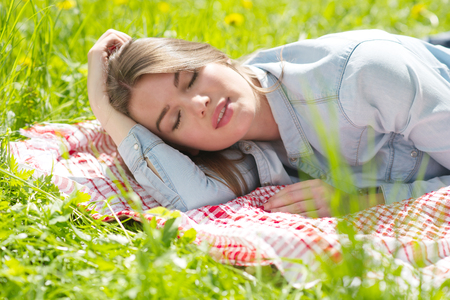 Foto de Beautiful young woman sleeping on fresh spring grass in park - Imagen libre de derechos