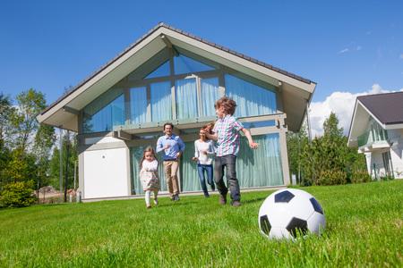 Foto für Family with children playing football on the backyard lawn near their house - Lizenzfreies Bild