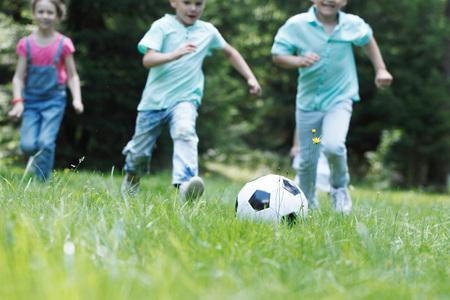 Photo pour Happy children playing football in summer park - image libre de droit