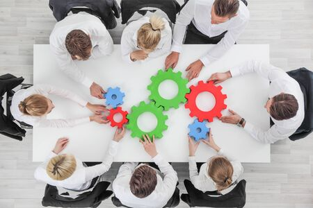 Business team meeting cooperation concept top view group people on table with cogwheels