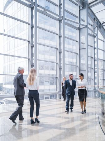 Photo pour Business people walking in a modern hall of office building - image libre de droit