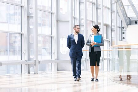 Photo for Businessman and businesswoman walk together and talk about business holding coffee in hand - Royalty Free Image