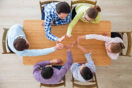Photo pour Coworkers doing high five sitting at the office table, top view - image libre de droit