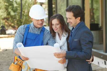 Photo pour Foreman shows house design plans to a young couple at construction site outdoors - image libre de droit