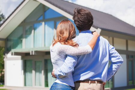Photo pour Happy couple stand outdoors hug and look at their new house - image libre de droit