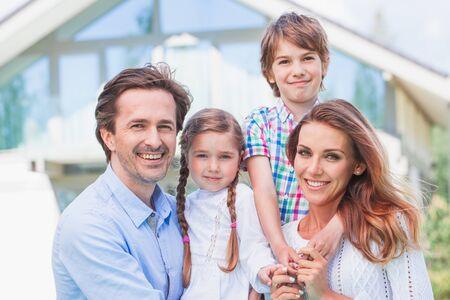 Photo pour Portrait of happy family of four people in front of house - image libre de droit