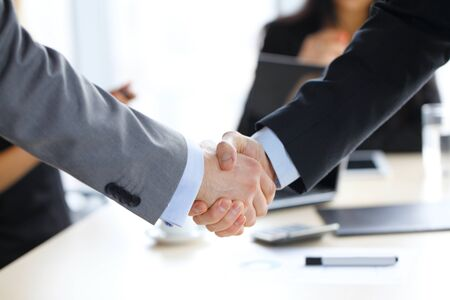 Photo pour Business handshake at office , working team on background - image libre de droit