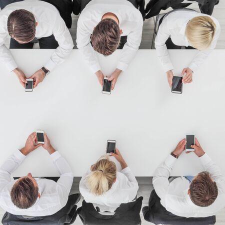 Foto de Business people using smartphones sitting at table in office, white copy space background - Imagen libre de derechos
