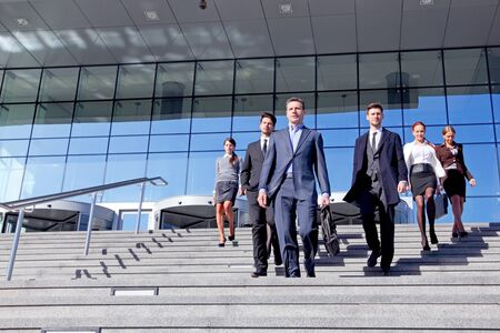 Foto de Group of business people and their leader walking down stairs outside office building successul deal negotiation concept - Imagen libre de derechos