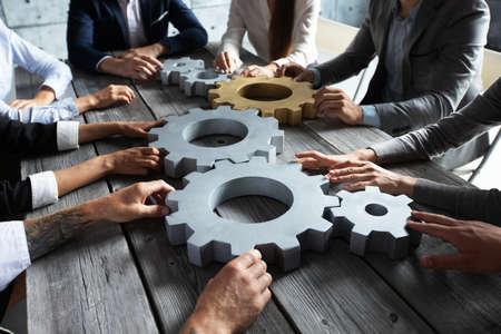 Photo pour Group of business people joining together silver and golden colored gears on table at workplace - image libre de droit