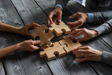 Photo pour Business people team sitting around meeting table and assembling wooden jigsaw puzzle pieces unity cooperation ideas concept - image libre de droit