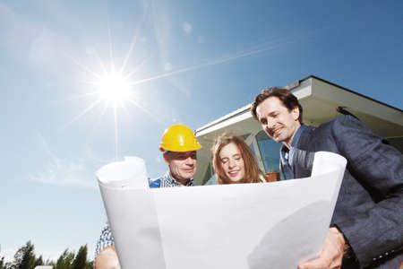 Foto de Worker shows construction plan to young couple outside house under construction sun in shining - Imagen libre de derechos