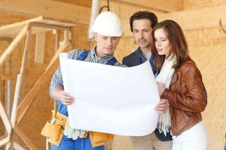 Photo pour Foreman showing house design construction plan to a happy young couple new house real estate concept - image libre de droit