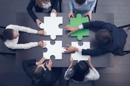 Foto de Group of business people assembling jigsaw puzzle at office table, top view, team support and help concept, green and white pieces - Imagen libre de derechos