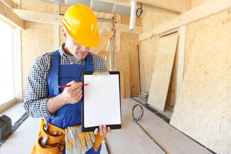Photo pour Worker showing document at construction site area, blank copy space for text - image libre de droit