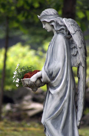 A statue of an angel holding a bed of flowers.