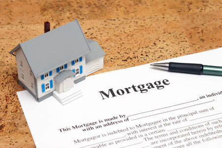 A conceptual image of a scale house and mortgage forms for the people buying a house.