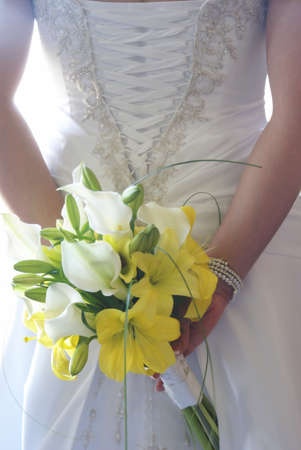 A young bride holds her flower bouquet behind her back.の写真素材