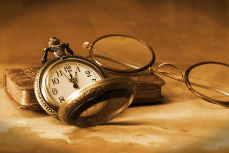 An antique pocket watch, glasses and bible come together in this vintage still life.