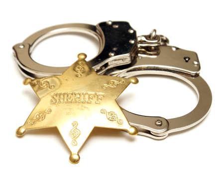 An isolated shot of a sheriff badge and pair of handcuffs.