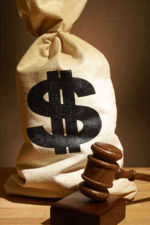 A bag of money and gavel represent many legal expenses.