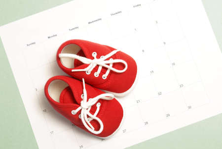 Photo for A pair of baby shoes on a monthly calendar to represent many parenting concepts. - Royalty Free Image
