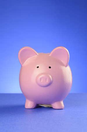 Photo pour A pink piggy bank facing frontwards over a blue gradient background. - image libre de droit